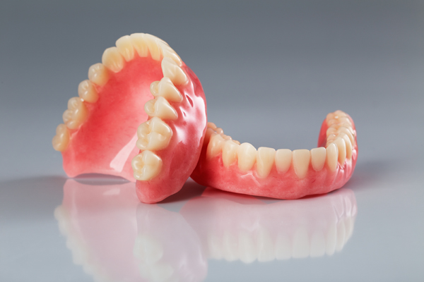 A set of dentures on a shiny gray background