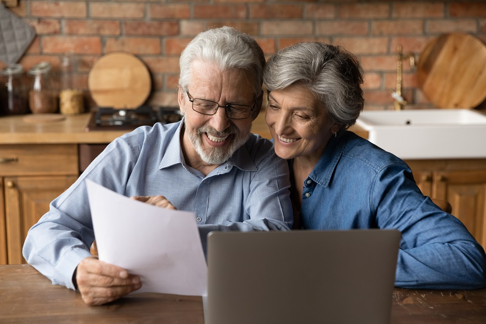 Happy elderly couple read good news in paper letter